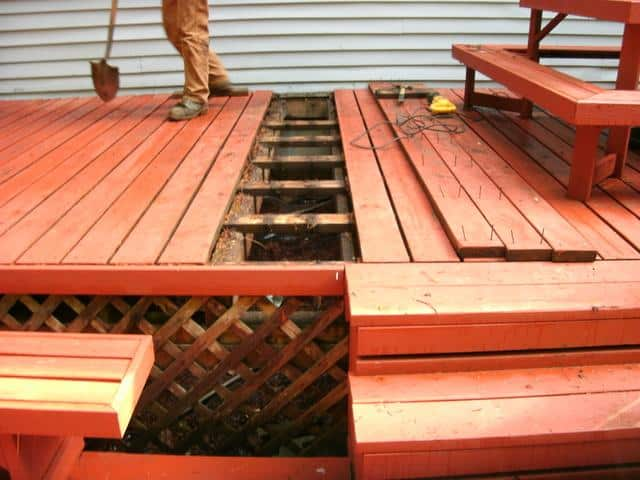 Deck boards removed to excavate area for push pier placement.